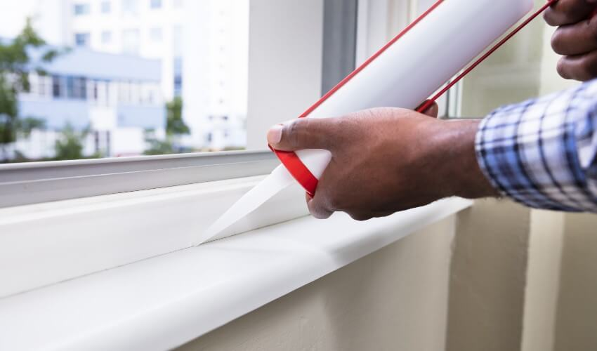 Close-up of hand applying silicone sealant on a window.