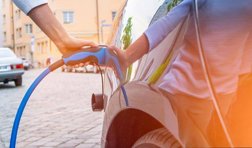 A hand holding a charger into an electric vehicle.