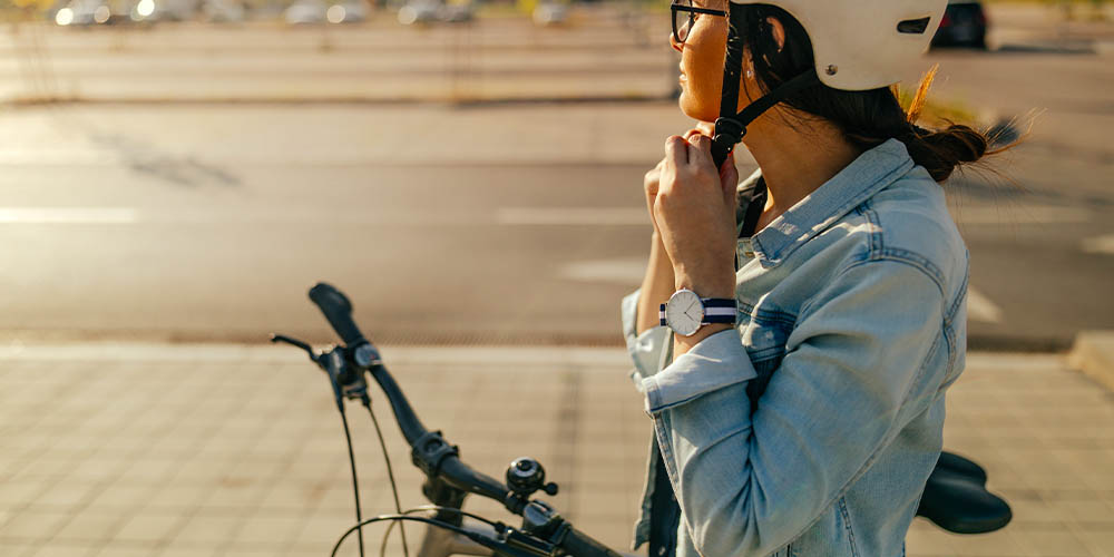 A woman fastens the strap on her bike helmet