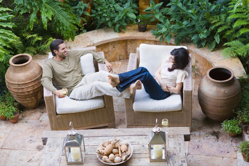 Couple seated on wicker chairs on designer inspired patio.