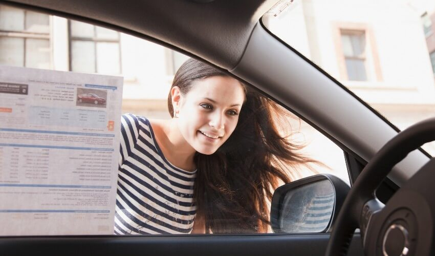 Woman peering past sales listing on car window to look at car interior.