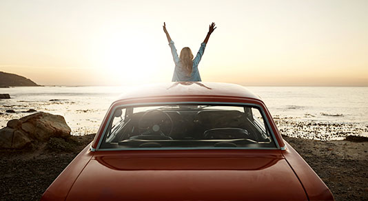 Young female sitting on hood of car with hands raised excited to enjoy the sunset and view of coast.