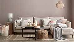 A neutral coloured living room with a sectional sofa, coffee table and other accessories